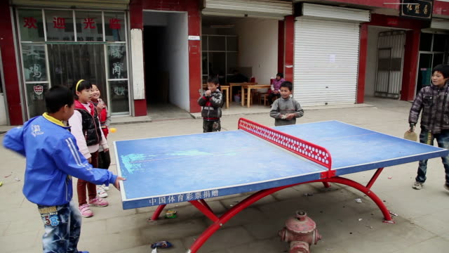 ms shot of children playing table tennis on wayside / hanzhong, shaanxi, china - bordtennis bildbanksvideor och videomaterial från bakom kulisserna