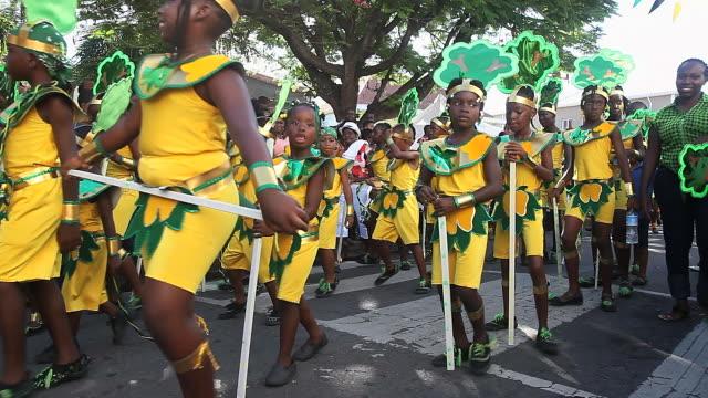 ms pan shot of childrens carnival parade audio / nevis, saint kitts and nevis - karibik stock-videos und b-roll-filmmaterial