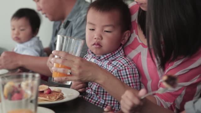 ms shot of chinese family eating together with boy drinking orange juice / los angeles, california, united states  - orangensaft stock-videos und b-roll-filmmaterial