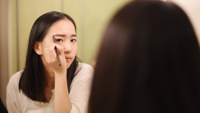vídeos de stock, filmes e b-roll de shot of chinese woman applying make up with blush in mirror / shanghai,china - blush