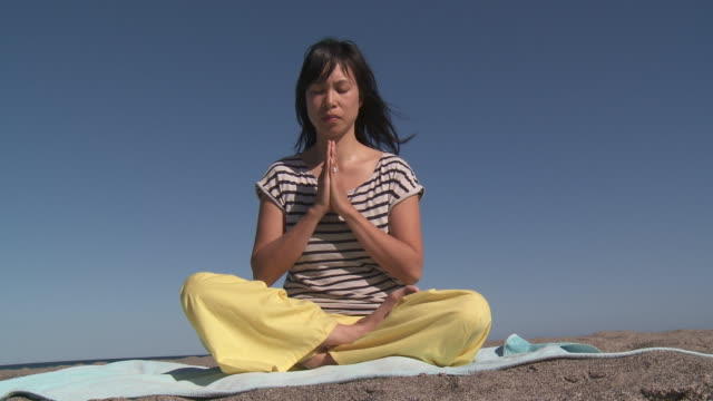 shot of chinese woman practicing yoga on the beach - gambe incrociate video stock e b–roll