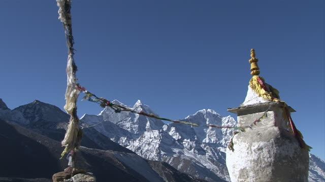 ws shot of chorten with prayer flags and mountain range (thamaserku & kangtegra) / dingboche, khumbu region, nepal - khumbu stock videos and b-roll footage