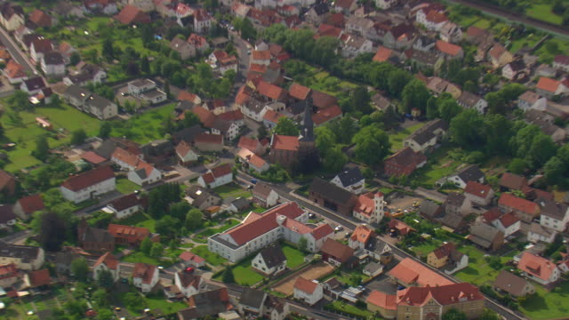 ms aerial zi shot of church and houses at obersuhl / germany - zoom in stock videos & royalty-free footage