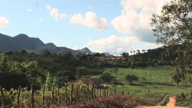 vídeos de stock, filmes e b-roll de ms zo shot of church and landscape around it with dirt road / jacobina, bahia, brazil - estrada rural