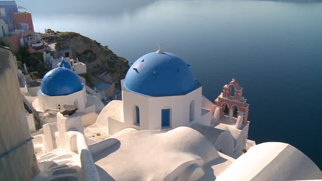 ms tu shot of church at village oia with ocean / santorini, cyclades, greece - oia santorini stock videos & royalty-free footage