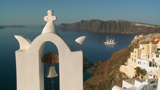 CU Shot of church bell with ship movinf in Ocean at village Oia / Santorini, Cyclades, Greece
