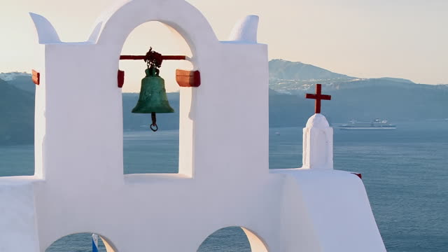 CU ZO Shot of church bells at village Oia with Ocean / Santorini, Cyclades, Greece