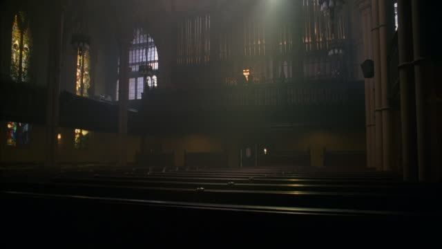 MS ZI TU Shot of Church interior and stained glass windows with Person playing piano in Church