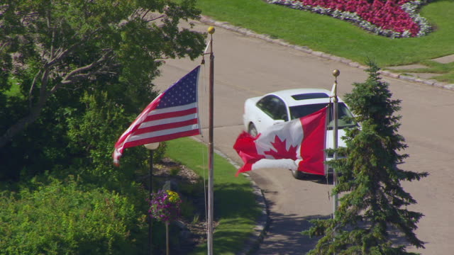 MS AERIAL TD TS Shot of Circle flag of United States of America and Canadian flag at International Peace Garden / Dunseith, North Dakota, United States