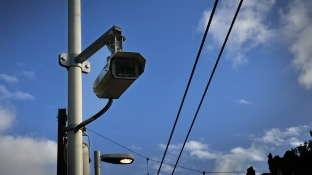 cu t/l shot of circuit television camera surveillance people reflecting in lens power cables through frame white clouds in blue sky in back side / london, greater london, united kingdom - power line stock videos & royalty-free footage