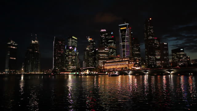 MS Shot of city from across water cool sky at night / Singapore