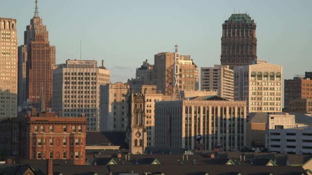 vidéos et rushes de ms pan shot of city sky line with sun shining on buildings / detroit, michigan, united states - détroit michigan