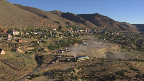 ms aerial shot of city with construction site and buildings and church built into side of mountain / virginia city, nevada, united states - nevada stock videos & royalty-free footage