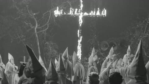 vidéos et rushes de ms td pan shot of clan rally in woods with cross burning - injustice