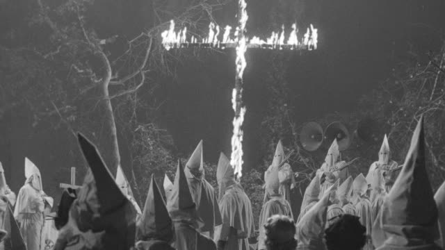 stockvideo's en b-roll-footage met ms td pan shot of clan rally in woods with cross burning - racisme