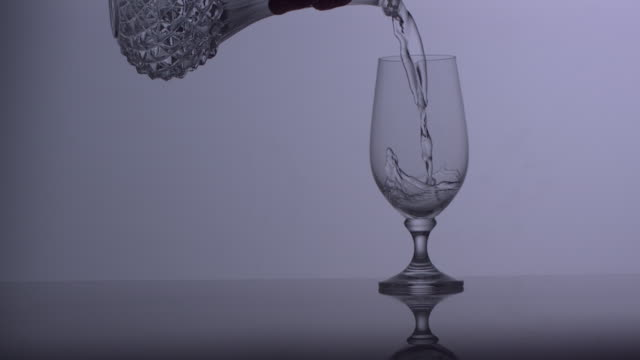 ms slo mo shot of clear liquid pouring into glass from decanter / united kingdom - decanter stock videos & royalty-free footage