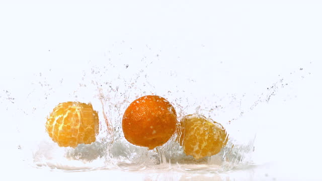 CU SLO MO Shot of Clementines, citrus reticulata, Fruits falling and splashing on Water against White Background / Calvados, Normandy, France