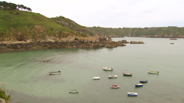 WS PAN Shot of Cliff edge with bots in water / St. Peter Port, Guernsey, United Kingdom