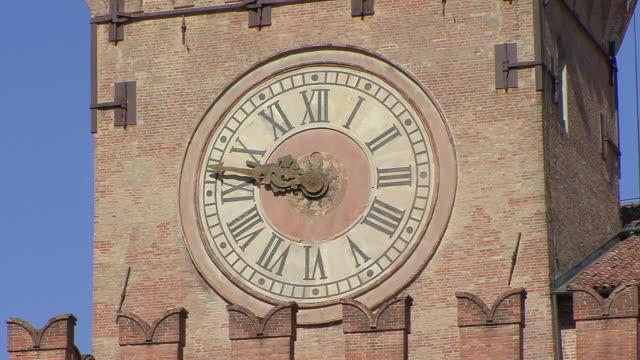 cu shot of clock in medieval clocktower above city hall / bologna, emilia romagna, italy - romersk siffra bildbanksvideor och videomaterial från bakom kulisserna