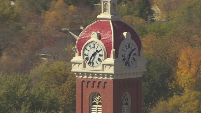cu aerial zo shot of clock tower and pull out to cathedral of holy trinity / new ulm, minnesota, united states - clock tower stock videos and b-roll footage