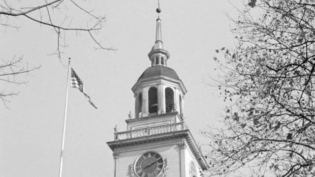 stockvideo's en b-roll-footage met ms shot of clock tower with american flag flying next to it with some tree limbs - kerktoren