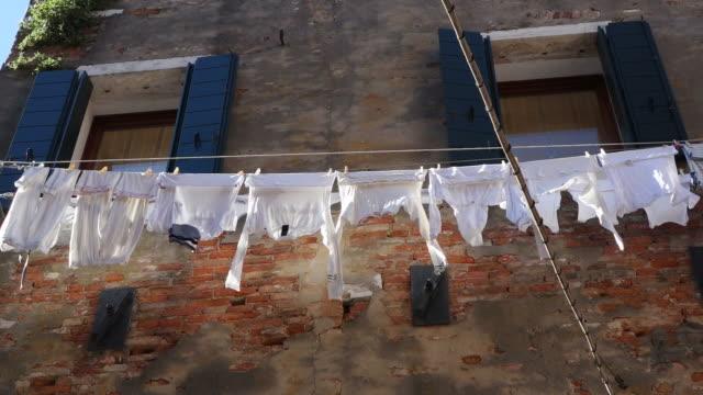 stockvideo's en b-roll-footage met ms la shot of cloth lines hanging on wire between houses, arsenale / venice, veneto, italy - wasknijper