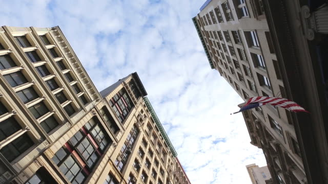 ms t/l shot of cloud migrating over soho loft buildings with american flag waving by wind / new york, united states - 屋根裏部屋点の映像素材/bロール