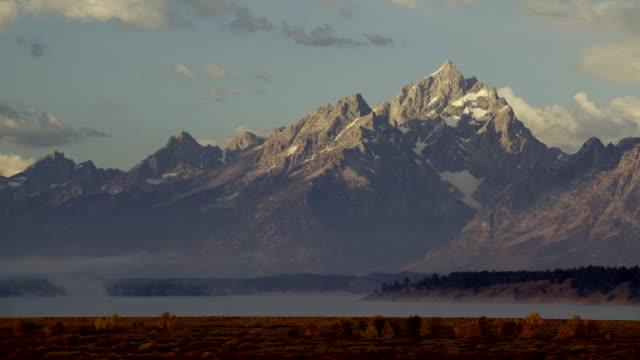 ws t/l shot of clouds and shadows move over snow peaked mountains at grand teton national park / jackson hole, wyoming, united states - grand teton bildbanksvideor och videomaterial från bakom kulisserna