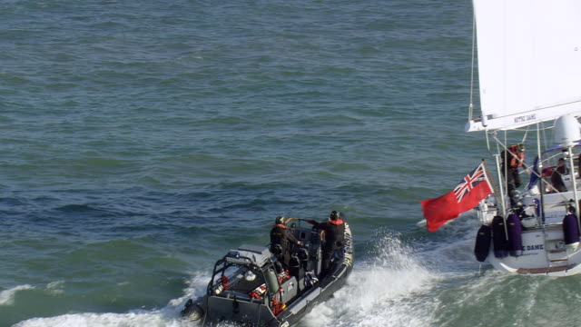 WS AERIAL TS Shot of coast guard entering into rescue motor boat from sail boat / Suffolk, France