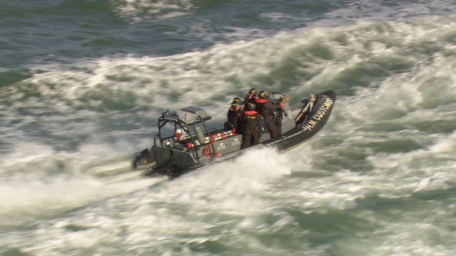 ms aerial ts shot of coast guards with customs rescue boat moving ahead in sea / suffolk, france - 救助隊点の映像素材/bロール
