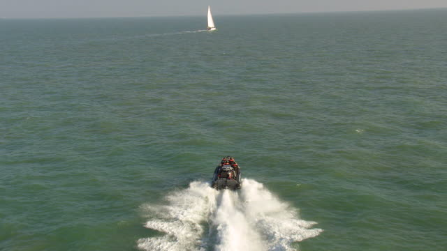 WS AERIAL Shot of coast guards with customs rescue boat moving ahead in sea / Suffolk, France