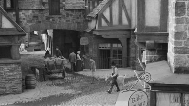 ms pan shot of cobblestone streets and old shops and few people in town square and herder leads herd of sheep - market reenactment stock videos & royalty-free footage