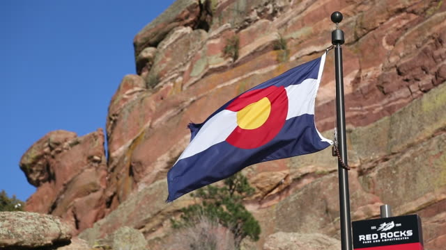 ms shot of colorado flag with red rocks in background / denver, colorado, united states - red rocks stock videos & royalty-free footage