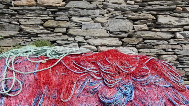 MS Shot of colorful fishing net at slate stone wall / Centuri Port, Corsica, France