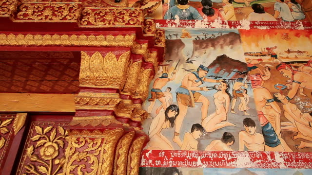 ms pan shot of colorful gory paintings on exterior buddhist temple wall / luang prabang, laos - female likeness stock videos & royalty-free footage