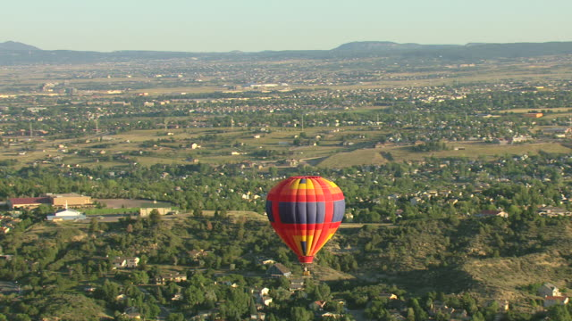 MS AERIAL Shot of colorful hot air balloon flying over city and suburban houses / Colorado Springs, Colorado, United States
