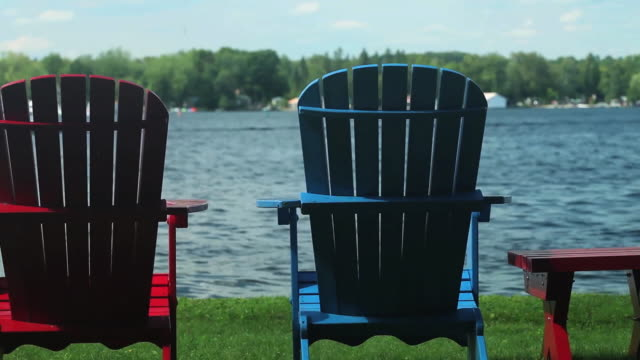 ms pan shot of colorful muskoka chairs at side of lake  / bobcaygeon, ontario, canada - アディロンダックチェア点の映像素材/bロール