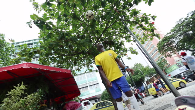 ms shot of coloured guy with brazilian trikot playing freestyle football at a street corner/ rio de janeiro, brazil  - one mid adult man only stock videos & royalty-free footage