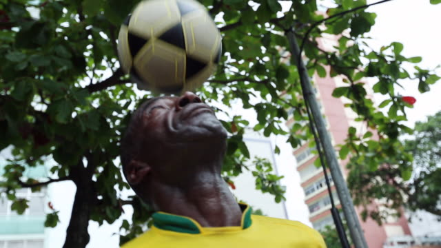 MS TU TD Shot of coloured guy with brazilian trikot playing freestyle football at street corner / Rio de Janeiro, Brazil