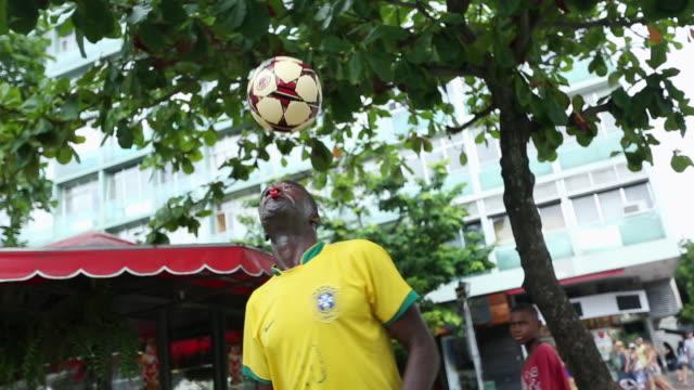vídeos de stock, filmes e b-roll de ms ts shot of coloured guy with brazilian trikot playing freestyle football at street corner, posing and whisteling / rio de janeiro, brazil  - termo esportivo