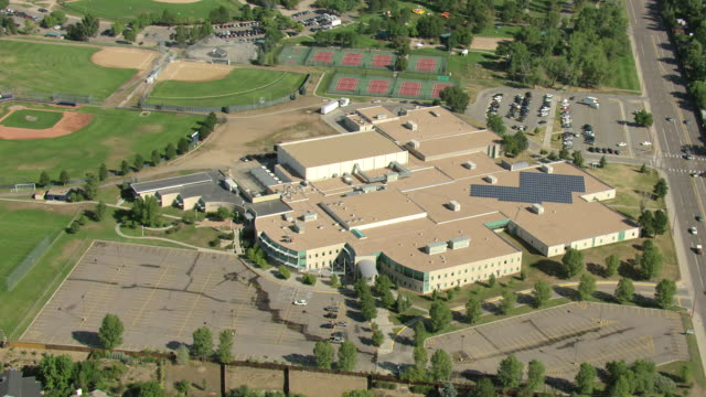 ms aerial shot of columbine high school, baseball fields surrounding school and hope columbine memorial library sign on building with courtyard / littleton, colorado, united states - sekundarstufe stock-videos und b-roll-filmmaterial