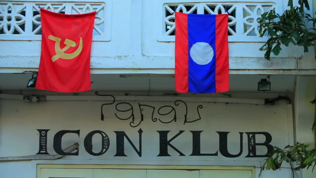 ms shot of communist and lao flag hanging on white balcony / luang prabang, laos - communist flag stock videos & royalty-free footage