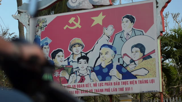 ms shot of communist party propaganda poster / hoi an, quang nam, viet nam - comunismo video stock e b–roll