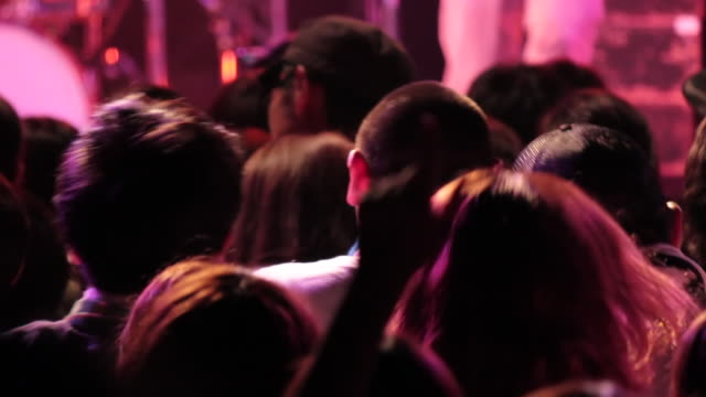 ms shot of concert crowd hands up and jumping / ebisu, tokyo, japan - 若者文化点の映像素材/bロール