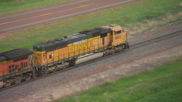 MS AERIAL TS Shot of Conductor car pulling BNSF train going through countryside in Sheridan County / Wyoming, United States