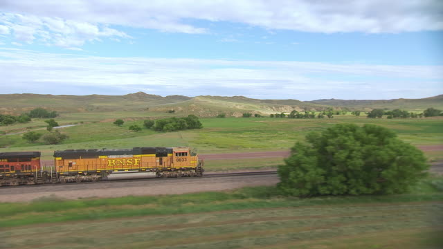 vidéos et rushes de cu aerial zo ts shot of conductor car pulling bnsf train going through countryside in sheridan county and circle around to front of train / wyoming, united states - wyoming