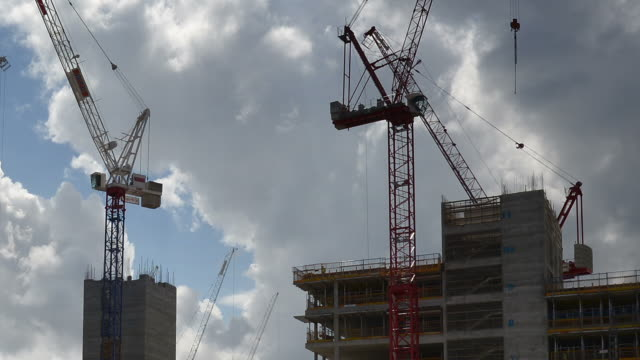 """CU LA T/L Shot of Construction Tower Cranes working on early stage of office building construction billowing white and grey clouds on blue sky / London, Greater London, United Kingdom"""