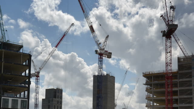 'MS LA T/L Shot of Construction Tower Cranes working on early stage of office building construction billowing white and grey clouds on blue sky / London, Greater London, United Kingdom'