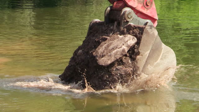 cu ts shot of construction waste material immersing into water at bridge construction site preparing demolition of old bridge / wiltingen, rhineland palatinate, germany - construction material stock videos & royalty-free footage