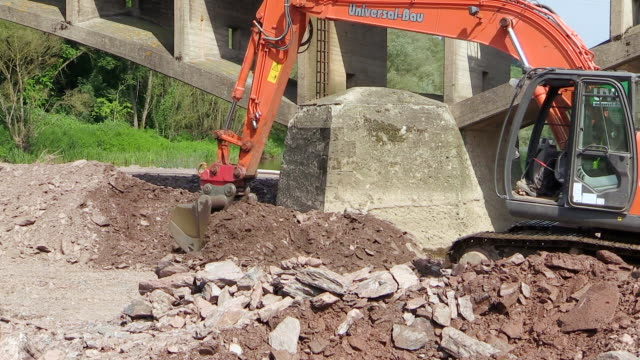 ms ts shot of construction waste material immersing into water at bridge construction site preparing demolition of old bridge / wiltingen, rhineland palatinate, germany - construction material stock videos & royalty-free footage